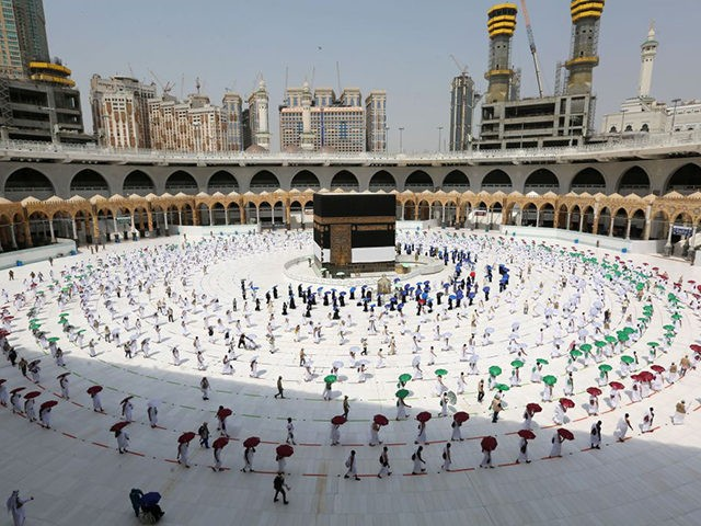 TOPSHOT - A picture taken on July 29, 2020 shows pilgrims holding coloured umbrellas along matching coloured rings separating them as a COVID-19 coronavirus pandemic measure while circumambulating around the Kaaba, Islam's holiest shrine, at the centre of the Grand Mosque in the holy city of Mecca, at the start …