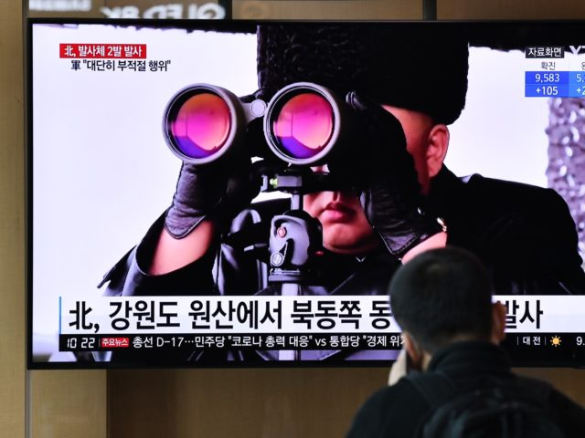 A man watches a news broadcast showing file footage of North Korean leader Kim Jong Un, at a railway station in Seoul on March 29, 2020. - North Korea fired what appeared to be two short-range ballistic missiles off its east coast on March 29, the fourth such launch this …