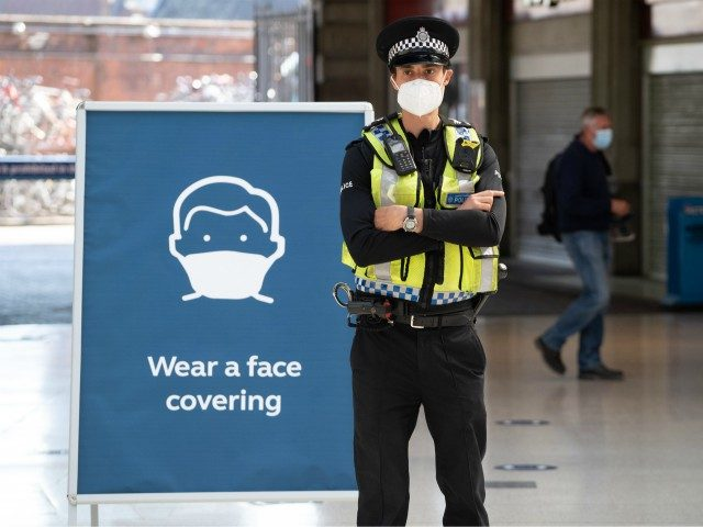 A police officer wears a face mask as he stands on the concourse at Waterloo Station in London on June 15, 2020 after new rules make wearing face coverings on public transport compulsory while the UK further eases its coronavirus lockdown. - New coronavirus pandemic rules coming into force on …