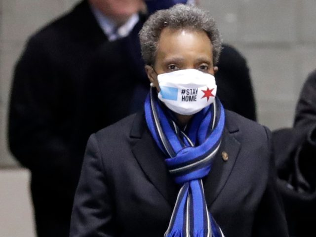"Chicago Mayor Lori Lightfoot, left, wears a mask as she heads to a news conference in Hall A of the COVID-19 alternate site at McCormick Place in Chicago, Friday, April 10, 2020. The ""alternative care facility"" is designed to relieve pressure on city hospitals from rapidly mounting COVID-19 cases. (AP …"