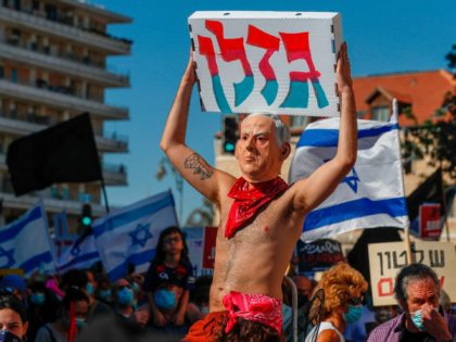 An Israeli protester, wearing swim suits and a mask with the effigy of Pime Misiter Benjamin Netanyahu, takes part in a demonstration against him outside his official residence in Jerusalem on July 24, 2020. - Public confidence in the government has been dented by a recent wave of contradictory emergency …
