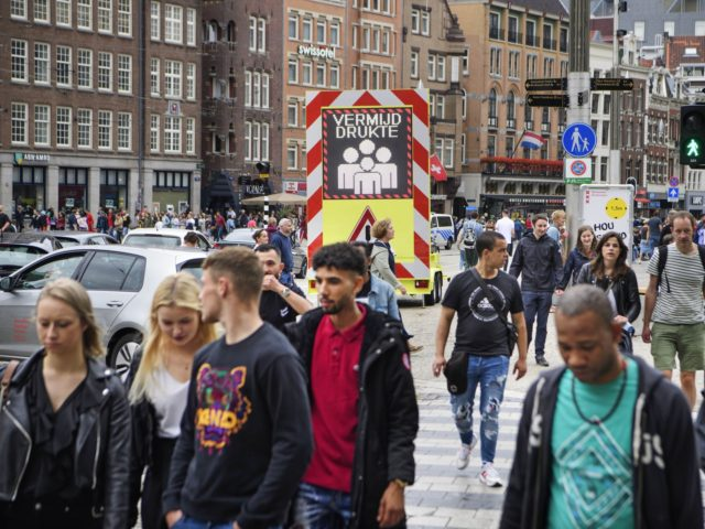 no masks for Day trippers and tourists walk in Amsterdam on July 25, 2020 as the municipality has stricter supervision over the weekend and one-way traffic was set up for pedestrians on a certain section of the Kalverstraat shopping street in Amsterdam due to the increasing number of infections caused ...