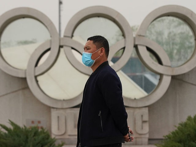 BEIJING, CHINA - MARCH 25: A Chinese man wears a protective mask as he walks past the Olympics rings at the Olympic park on March 25, 2020 in Beijing, China. The 2020 Tokyo Olympics have been postponed to no later than the summer of 2021 because of the coronavirus (COVID-19) …
