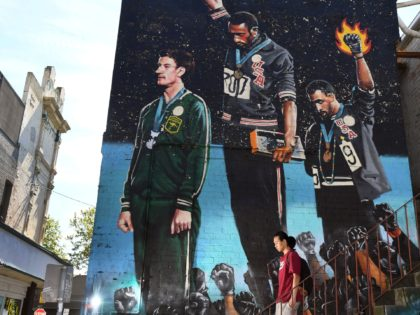 A photo taken in Melbourne on October 8, 2018, shows a man walking past a giant mural of Australian runner Peter Norman with US sprinters Tommie Smith and John Carlos. - When a principled Peter Norman stood on the podium alongside two Americans in their famous Black Power salute at …