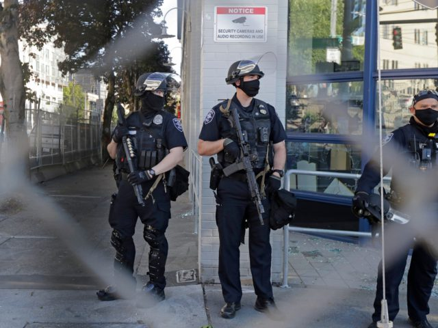 Seattle Police officers hold weapons as they stand guard outside the East Precinct Building, Sunday, July 19, 2020 in Seattle. Protesters broke windows at the building earlier in the afternoon. (AP Photo/Ted S. Warren)
