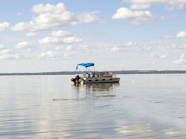 horizontal image of a pontoon boat coasting on a beautiful blue lake under clear blue sky in the summer time.