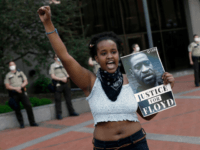 In this May 28, 2020 file photo, a protester holds a photo of George Floyd during a protest in Minneapolis over Floyd's death. Video from the body cameras of two officers charged in the death of Floyd is being made available for public viewing by appointment on Wednesday, July 15 …