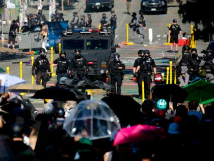 "Protesters confront police at the former location of the Capitol Hill Organized Protest (CHOP) after a ""Youth Day of Action and Solidarity with Portland"" demonstration in Seattle, Washington on July 25, 2020. - Police in Seattle used flashbang grenades and pepper spray Saturday against protesters who set fire to construction …"