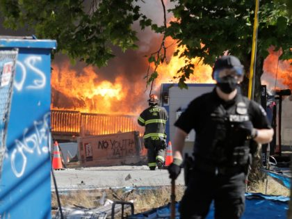 Construction buildings burn near the King County Juvenile Detention Center, Saturday, July 25, 2020, in Seattle, shortly after a group of protesters left the area. A large group of protesters were marching Saturday in Seattle in support of Black Lives Matter and against police brutality and racial injustice. Protesters broke …