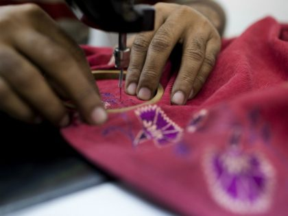 An Indian labourer sews patterns at the April Cornell clothing factory in Noida on the outskirts of New Delhi on October 16, 2012. The April Cornell company exports 50 percent of their clothing and linen production to the USA and Canada, and the rest to European Union countries. India's industrial …