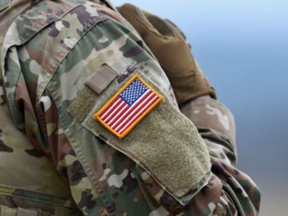 A US flag is pictured on a soldier's uniform during an artillery live fire event by the US Army Europe's 41st Field Artillery Brigade at the military training area in Grafenwoehr, southern Germany, on March 4, 2020. - The 41st Field Artillery Brigade plans, prepares, executes and assesses operations to …