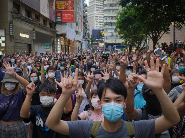 """Protesters against the new national security law gesture with five fingers, signifying the """"Five demands - not one less"""" on the anniversary of Hong Kong's handover to China from Britain in Hong Kong, Wednesday, July. 1, 2020. Hong Kong marked the 23rd anniversary of its handover to China in 1997, …"""