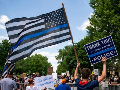 "ST PAUL, MN - JUNE 27: A demonstrator holds a ""Thin Blue Line"" flag and a sign in support of police during a protest outside the Governors Mansion on June 27, 2020 in St Paul, Minnesota. A group called ""Bikers for 45"" advocating a pro-police stance arranged the protest and …"