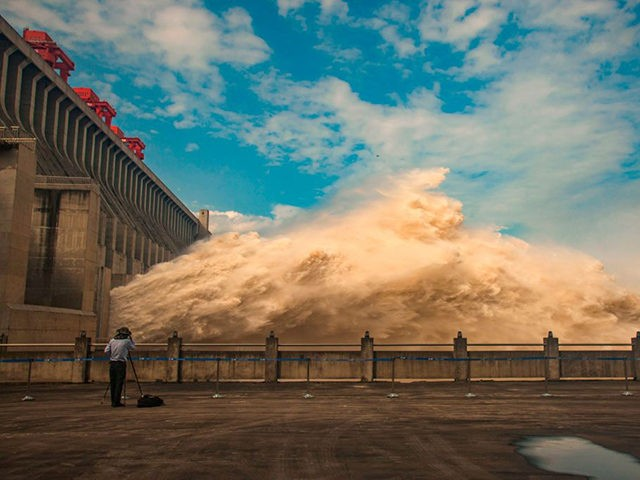 This photo taken on July 19, 2020 shows a person taking photos while water is released from the Three Gorges Dam, a gigantic hydropower project on the Yangtze river, to relieve flood pressure in Yichang, central China's Hubei province. - Rising waters across central and eastern China have left over …