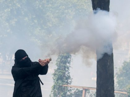A protester throws a firecrackers to anti riot police officers in front of regional Prefecture, during a demonstration in Nantes, on June 16, 2020, as part of a nationwide day of protests to demand better working conditions for health workers. (Photo by Loic VENANCE / AFP) (Photo by LOIC VENANCE/AFP …