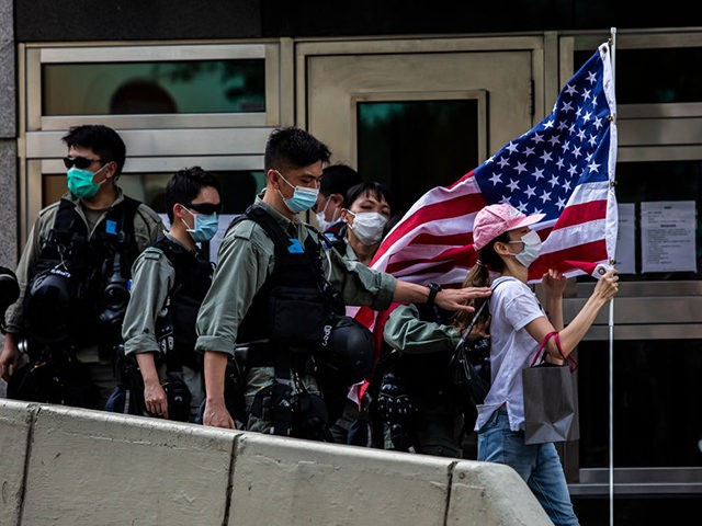 Police remove a woman holding a US flag from outside the US consulate during a march to celebrate US Independence Day in Hong Kong on July 4, 2020. (Photo by ISAAC LAWRENCE / AFP) (Photo by ISAAC LAWRENCE/AFP via Getty Images)
