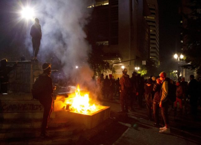 In this July 4, 2020, file photo, protesters gather near a fire in downtown Portland, Ore. Oregon's largest city is in crisis as violent protests have wracked downtown for weeks. The mayor can't bring the council along on cracking down because of very liberal council members and no matter what …