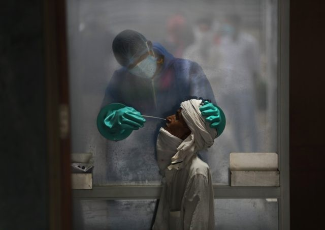 A health worker takes a nasal swab of a person for a COVID-19 test at a hospital in New Delhi, India, Monday, July 6, 2020. (AP Photo/Manish Swarup)