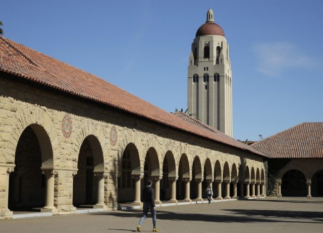 In this March 14, 2019, file photo, people walk on the Stanford University campus beneath Hoover Tower in Stanford, Calif. A week after revoking sweeping new restrictions on international students, federal immigration officials on Friday, July 24, 2020, announced that new foreign students will be barred from entering the United …