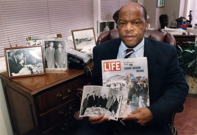 Congressman John Lewis poses in his Atlanta office with two of his favorite items from his collection of memorabilia from his younger days as a civil rights activist in the 1960s. He is holding a Life Magazine cover picturing the famous Selma march in 1965. (He is in this photo …