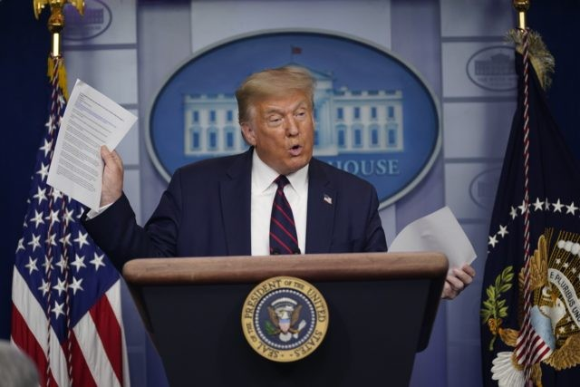 President Donald Trump holds articles as he speaks during a news conference at the White House, Thursday, July 30, 2020, in Washington. (AP Photo/Evan Vucci)