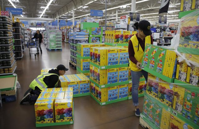 In this Nov. 27, 2019, file photo Jayln Martin, right, and Dan Villegas stock items in preparation for a holiday sale at a Walmart Supercenter in Las Vegas. On Friday, Jan. 31, 2020, the Labor Department reports on wages and benefits for U.S. workers during the Oct.-Dec. quarter. (AP Photo/John …