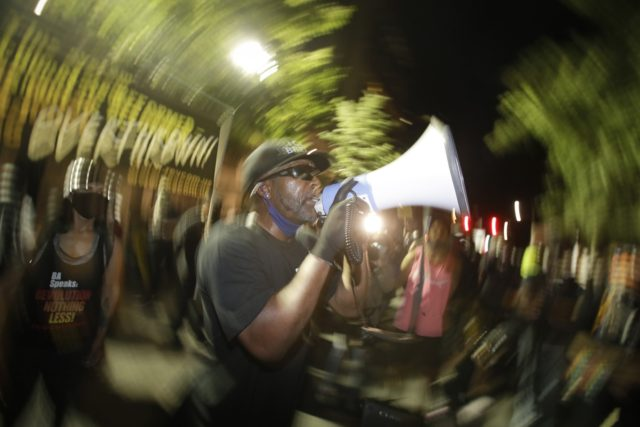 A speaker addresses the crowd during a Black Lives Matter protest at the Mark O. Hatfield United States Courthouse Thursday, July 30, 2020, in Portland, Ore. After days of clashes with federal police, the crowd outside of the federal courthouse remained peaceful Thursday night. (AP Photo/Marcio Jose Sanchez)