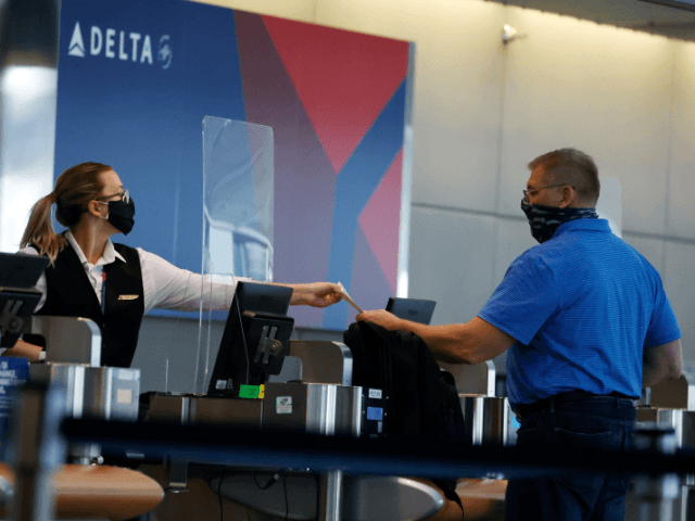 In this July 22, 2020 photo, a ticketing agent for Delta Airlines hands a boarding pass to a passenger as he checks in for a flight in the main terminal of Denver International Airport in Denver. .Air travel has collapsed because of the virus pandemic, and airlines are trying to …