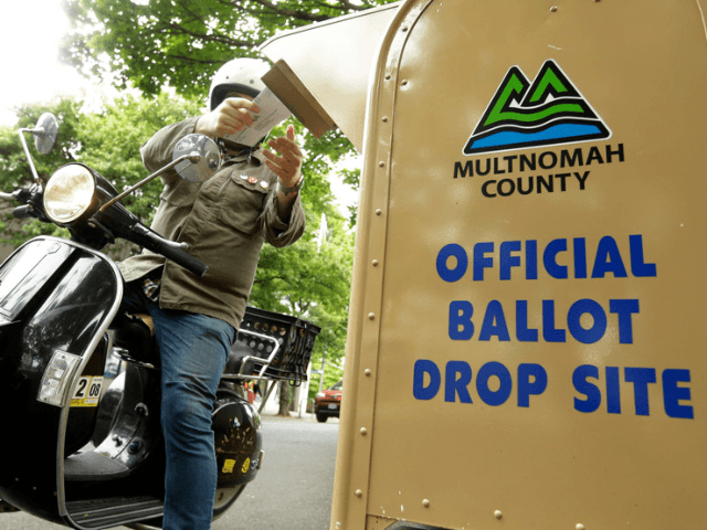 In this May 15, 2018, file photo, a voter drops off his ballot on the day of Oregon's primary election at a drive-by, drop-off station in Portland, Ore. Running an election by mail is a major undertaking, involving the U.S. Postal Service, armies of volunteers and even librarians. But for …