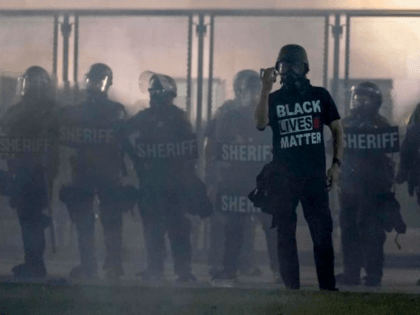 In this Aug. 25, 2020 file photo, a protester holds up a phone as he stands in front of authorities in Kenosha, Wis. Until the police shooting of Jacob Blake, the bedroom community of Kenosha has been largely untouched by the level of demonstrations that had been seen in nearby …