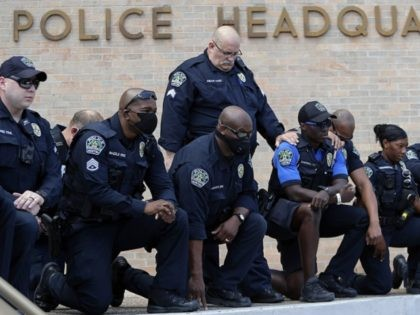 Members of the Austin Police Department kneel in front of demonstrators who gathered in Austin, Texas, Saturday, June 6, 2020, to protest the death of George Floyd, a black man who was in police custody in Minneapolis. Floyd died after being restrained by Minneapolis police officers on Memorial Day. (AP …