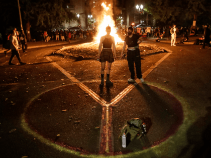 Demonstrators draw a peace sign in front of a fire during a Black Lives Matter protest at the Mark O. Hatfield United States Courthouse Tuesday, July 28, 2020, in Portland, Ore. (AP Photo/Marcio Jose Sanchez)