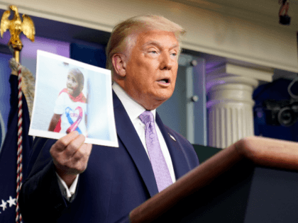 President Donald Trump holds a photo of LeGend Taliferro as he speaks at a news conference in the James Brady Press Briefing Room at the White House, Thursday, Aug. 13, 2020, in Washington. LeGend Taliferro, 4, was shot and died while he slept in his apartment in Kansas City, Mo., …