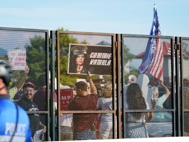 Protesters stand outside of the security fence before Democratic presidential candidate former Vice President Joe Biden speaks during the fourth day of the Democratic National Convention, Thursday, Aug. 20, 2020, at the Chase Center in Wilmington, Del. (AP Photo/Carolyn Kaster)