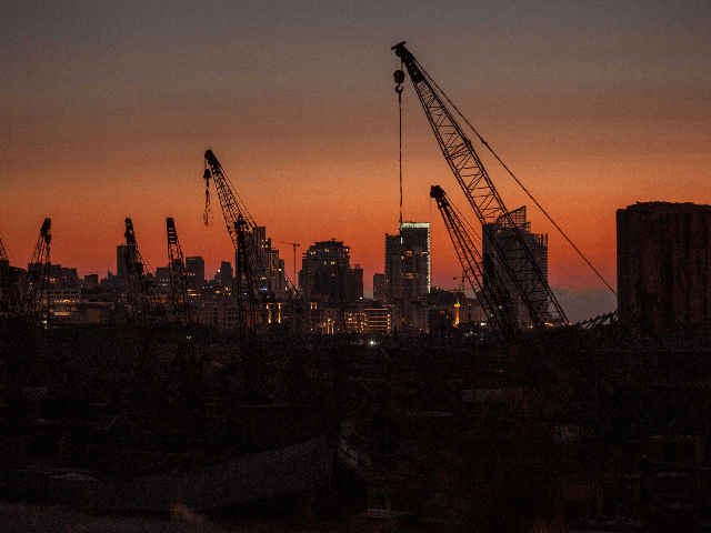 Rows of damaged cranes stand at the site of the Aug. 4 deadly blast in the port of Beirut that killed scores and wounded thousands as the sun sets over the capital Beirut, Lebanon, Tuesday, Aug. 25, 2020. (AP Photo/Hassan Ammar)