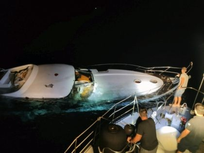 In this photo provided on Wednesday, Aug. 26, 2020 by the Greek Coast Guard, a half-sunken yacht is photographed during a search and rescue operation by the Greek authorities west of the small island of Halki, near Rhodes, southeastern Greece. A total of 96 people were rescued from the sea …