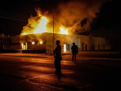 Police stand near a department of corrections building that was on fire during protests, Monday, Aug. 24, 2020, in Kenosha, Wis., sparked by the shooting of Jacob Blake by a Kenosha Police officer a day earlier. (AP Photo/Morry Gash)