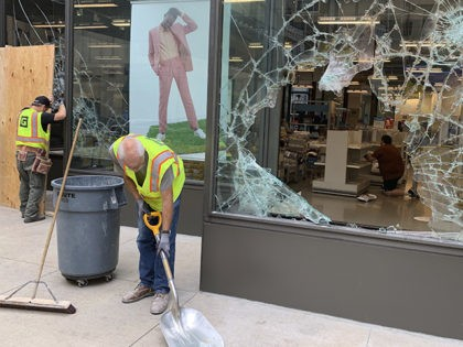 A worker shovels broken glass outside of Nordstrom Rack in downtown Minneapolis on Thursday, Aug. 27, 2020. An emergency curfew has expired and downtown Minneapolis was calm after unrest broke out overnight following what authorities said was misinformation about the suicide of a Black homicide suspect.(AP Photo/Jeff Baenen)