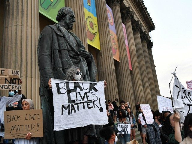A protester wearing a face mask holds a banner with the lettering reading 'Black lives matter' in Liverpool, northwest England, on June 2, 2020, during a demonstration after George Floyd, an unarmed black man, died after a police officer knelt on his neck during an arrest in Minneapolis, USA. - …