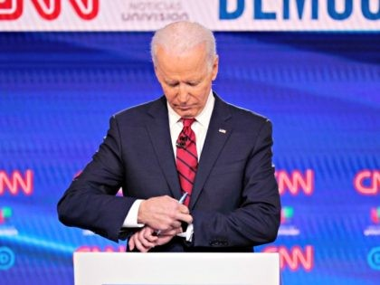 Former Vice President Joe Biden, check his watch during a commercial break as he participates in a Democratic presidential primary debate at CNN Studios, Sunday, March 15, 2020, in Washington. (AP Photo/Evan Vucci)