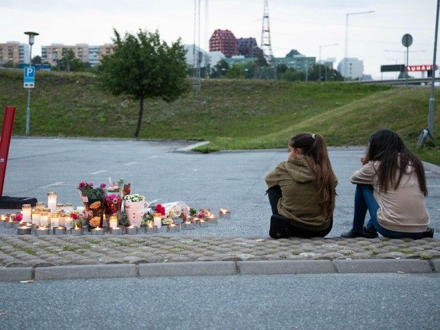 Two girls sit next to a makeshift memorial at the site where a twelve year old girl was shot near a petrol station in Botkyrka, south of Stockholm, on August 2, 2020. - The young girl with gunshot injuries was taken to hospital but later succumbed to her wounds. (Photo …