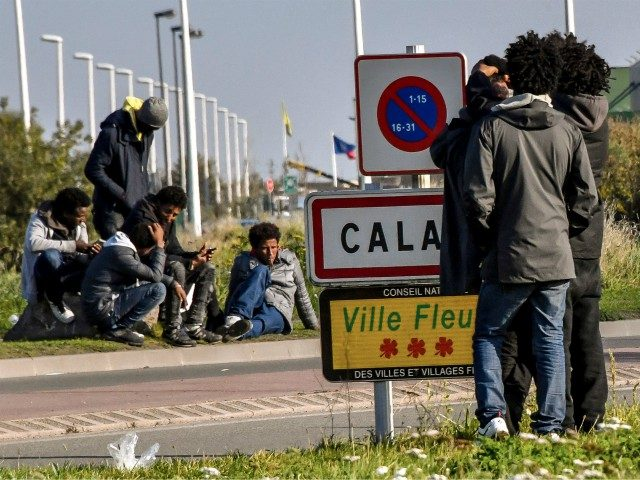"""Migrants gather at the entrance of the French northern city of Calais, on November 2, 2017, next to a lorry parking lot. In Calais, local associations put the number of migrants sleeping rough around the town at around 600-700 and they have sounded the alarm about """"catastrophic"""" conditions. / AFP …"""