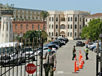 This July 9, 2020, file photo shows a correctional officer closing the main gate at San Quentin State Prison in San Quentin, Calif. California is giving more than 100,000 state inmates earlier release dates in its latest response to the pandemic, building on earlier steps that together could free nearly …