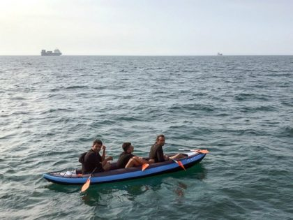 Three migrants who were attempting to cross The English Channel from France to Britain are seen as they drift in an inflatable canoe off the French coast at Calais on August 4, 2018, before being rescued by lifeguards of Les Sauveteurs en Mer (SNSM). (Photo by STR / AFP) (Photo …