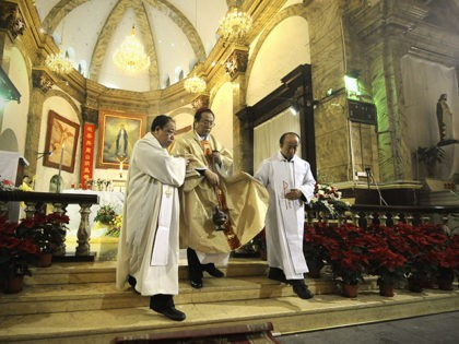 A Chinese archbishop, Li Shan(C) attends the Christmas Eve mass at a Catholic church in Beijing early on December 25, 2012. While China does not officially celebrate Christmas, its popularity continues to grow with non-Christians keen to see and feel the experience of Christmas. AFP PHOTO / WANG ZHAO (Photo …
