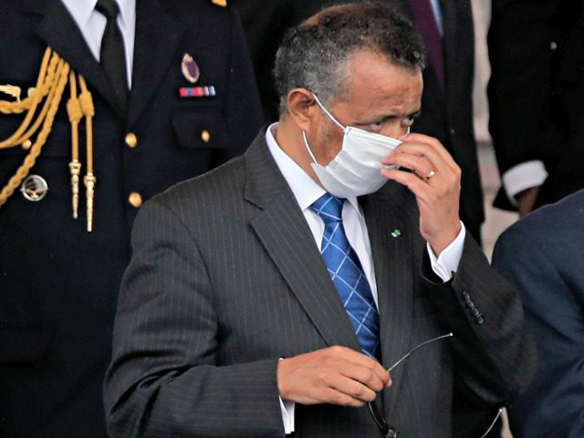 Director General of the World Health Organization, Tedros Adhanom Ghebreyesus, adjusts a face mask as he attends the Bastille Day military parade, Tuesday, July 14, 2020 in Paris. France are honoring nurses, ambulance drivers, supermarket cashiers and others on its biggest national holiday Tuesday. Bastille Day's usual grandiose military parade …