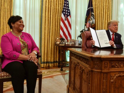 US President Donald Trump displays Alice Johnson's full pardon in the Oval Office of the White House in Washington, DC, on August 28, 2020. - Trump granted Johnson, a criminal justice reform advocate and former federal prisoner, a full pardon after commuting her sentence in 2018. (Photo by NICHOLAS KAMM …