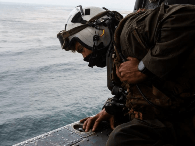 A search and rescue swimmer assigned to the @usnavy 's #USSMakinIsland looks out of an MH-60 Seahawk while conducting search and rescue relief operations, Friday, following an AAV-P7/A1 assault amphibious vehicle mishap off the coast of Southern California, Thursday.