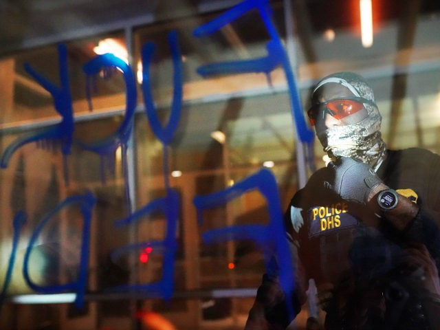 A federal officers reads the words Fuck Feds written in graffiti on the front of the Immigration and Customs Enforcement (ICE) detention facility early in the morning on August 21, 2020 in Portland, Oregon. For the second night in a row federal police clashed with crowds in South Waterfront after …