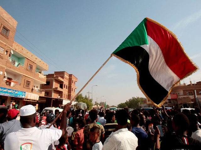 A man waves a Sudanese flag as Sudanese protesters demonstrate in Khartoum on July 25, 2019. - Sudanese protest leaders and their rebel partners have ended their differences over a power-sharing deal signed with the country's military rulers, vowing to work jointly for peace, a leading protest group said on …